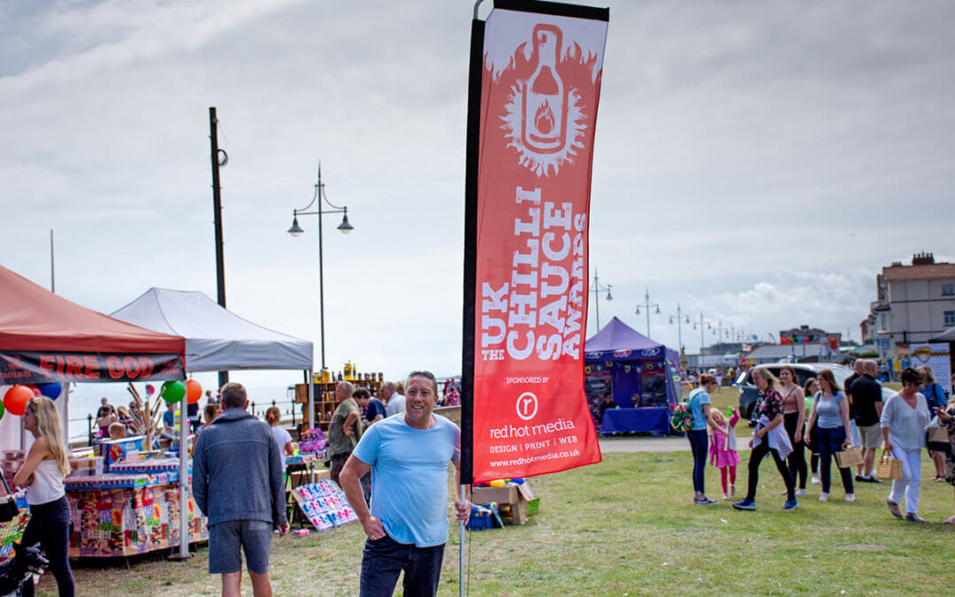 Photograph of Jason Oliver, Chilli Festival owner with a branded feather flag