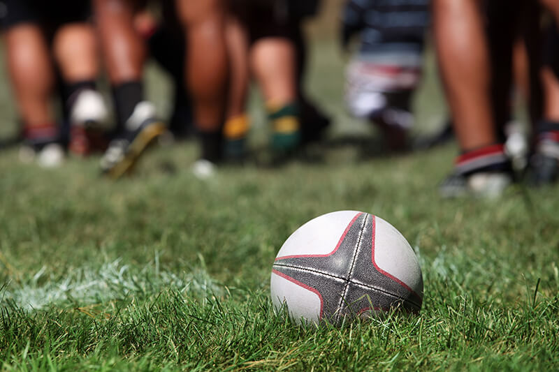 Photograph of rugby ball laying on grass with the legs of rugby players in the background