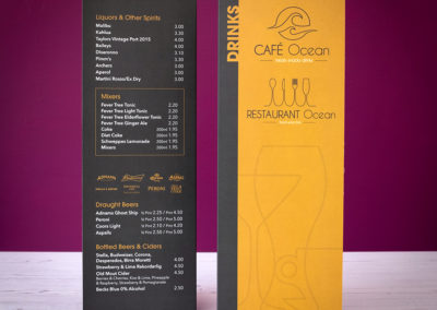 Photograph of a tall A4 folding Cafe Ocean drinks menu standing on white wooden floorboards with a purple wall in the background
