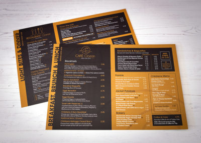 Photograph of an A4 Cafe Ocean food menu laying on white wooden floorboards